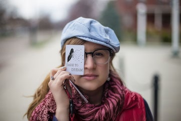 A long blond haired young woman wearing glasses and a blue cap holding a card that says Dare to Dream in front of her eye.